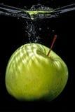 Grünen Sie Apfelspritzen, schwarzes Wasser Lizenzfreie Stockfotos