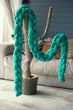Grünen Sie gestrickten Schal der Merinowolle hängt an einem künstlichen Baum I Stockbild