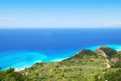 Grüner Abhang und beträchtliches blaues Meer auf der Insel von Lefkas Stockfotos