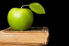 Grüner Apfel auf dem Buch getrennt Lizenzfreie Stockbilder