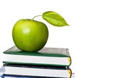 Grüner Apfel auf dem Lehrbuch getrennt Stockfotografie