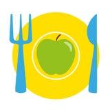 Grüner Apfel auf der gelben Platte mit blauer Gabel und Messer Stockfotos