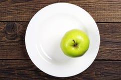 Grüner Apfel auf einer Platte Stockfotos