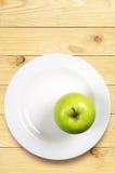 Grüner Apfel auf einer Platte Lizenzfreies Stockbild