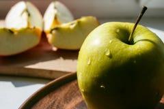 Grüner Apfel auf einer Platte in der Sonne Lizenzfreies Stockbild