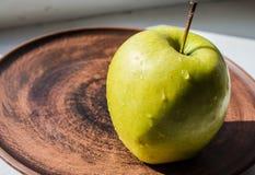 Grüner Apfel auf einer Platte in der Sonne Stockfotos