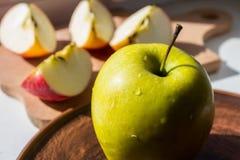 Grüner Apfel auf einer Platte in der Sonne Stockbild