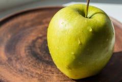 Grüner Apfel auf einer Platte in der Sonne Stockfoto