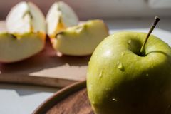Grüner Apfel auf einer Platte in der Sonne Lizenzfreies Stockfoto