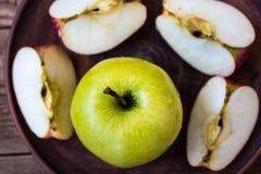 Grüner Apfel auf einer Platte auf hölzernem Hintergrund Stockfotos