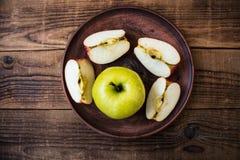 Grüner Apfel auf einer Platte auf hölzernem Hintergrund Stockbild