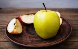 Grüner Apfel auf einer Platte auf hölzernem Hintergrund Stockbilder