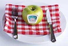 Grüner Apfel auf einer weißen Platte mit Messer und Gabel Lizenzfreies Stockbild
