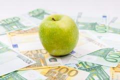Grüner Apfel auf Eurobanknoten streute den Boden - Europea aus Lizenzfreie Stockfotografie