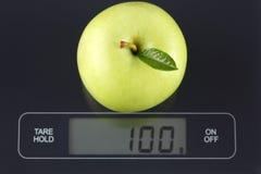 Grüner Apfel auf Küchenskala Stockbild