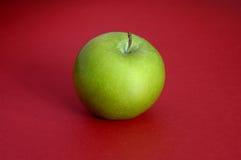Grüner Apfel auf rotem Hintergrund Stockfotografie