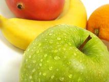 Grüner Apfel, Banane, Mangofrucht, orange Stockbilder