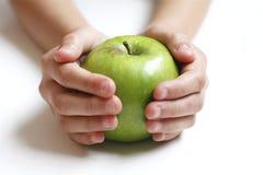 Grüner Apfel in den Händen des Kindes lizenzfreie stockbilder