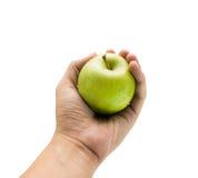 Grüner Apfel in der Hand auf lokalisiertem Hintergrund Lizenzfreie Stockbilder