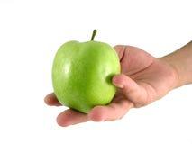 Grüner Apfel in der männlichen Hand Stockfotografie