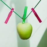 Grüner Apfel, der am Seil mit Clothespins hängt Stockbild