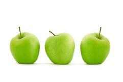 Grüner Apfel drei in der Reihe Stockbilder
