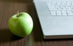 Grüner Apfel durch Laptop Lizenzfreie Stockfotos