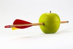 Grüner Apfel durchbohrt durch einen Pfeil Lizenzfreie Stockbilder
