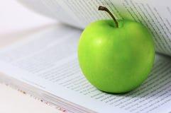 Grüner Apfel in einem Buch Lizenzfreies Stockfoto