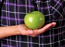 Grüner Apfel in einer Hand Stockbilder