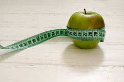 Grüner Apfel eingewickelt im Zentimeter auf weißem hölzernem Hintergrundesprit stockfoto