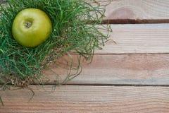 Grüner Apfel im Gras auf einem hölzernen Hintergrund Stockbild