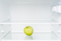 Grüner Apfel im leeren Kühlschrank Lizenzfreies Stockbild