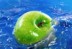 Grüner Apfel im Wasser Lizenzfreie Stockfotografie