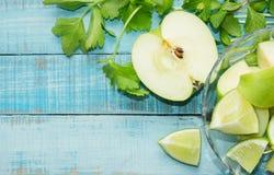 Grüner Apfel, Kalk geschnitten und Sellerie auf Purpleheart Stockbilder