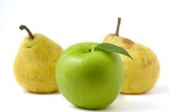 Grüner Apfel mit Blatt vor zwei Birnen Stockfotografie