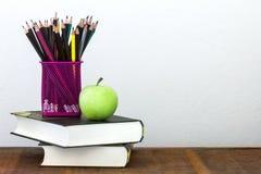 Grüner Apfel mit Bleistiftkasten auf Holztisch im Konzept der Studie Lizenzfreies Stockbild