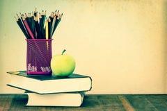 Grüner Apfel mit Bleistiftkasten auf Holztisch im Konzept der Studie Stockbild