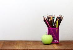 Grüner Apfel mit Bleistiftkasten auf Holztisch im Konzept der Studie Stockfotos