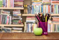 Grüner Apfel mit Bleistiftkasten auf Holztisch im Konzept der Studie Lizenzfreie Stockfotos