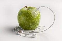 Grüner Apfel mit den Kopfhörern, die Musik mp3 hören Stockbild