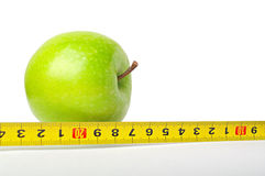 Grüner Apfel mit einem Messinstrument auf Weiß Lizenzfreies Stockfoto