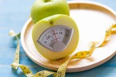 Grüner Apfel mit Gewichtsskala und messendes Band für das Abnehmen der gesunden Diät Lizenzfreie Stockfotos