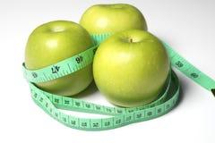 Grüner Apfel mit Maß die Länge auf weißem Hintergrund Stockbild