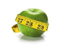 Grüner Apfel mit Maßband Stockfotografie