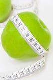 Grüner Apfel mit messendem Band Stockfotografie