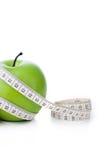 Grüner Apfel mit messendem Band Stockbild