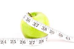 Grüner Apfel mit messendem Band Lizenzfreie Stockbilder