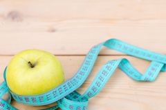 Grüner Apfel mit messendem Band auf hölzernem Hintergrund Nähren Sie Konzept Kopieren Sie Platz lizenzfreies stockfoto