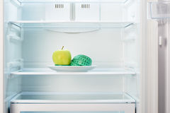 Grüner Apfel mit messendem Band auf weißer Platte im offenen leeren Kühlschrank Stockbilder